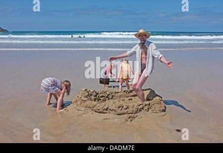 Mann Sadadndscastle am Strand mit Kindern bauen - Stockfoto