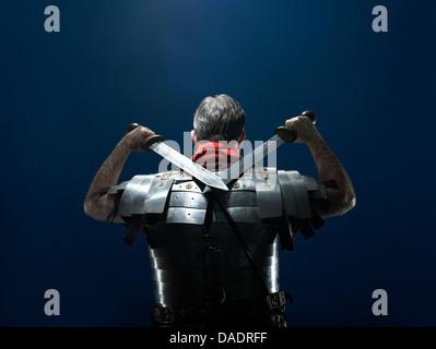 Rückansicht des Mannes in Rüstung Holding gekreuzt Schwerter - Stockfoto