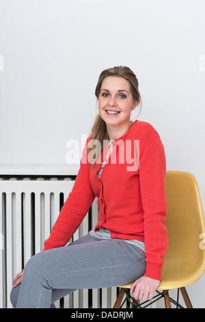 Porträt einer jungen Frau im roten Strickjacke Stockfoto