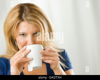 Mitte Erwachsene Frau trinken aus Becher Porträt - Stockfoto
