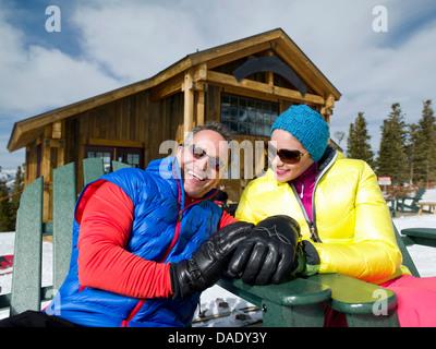Reifer Mann und junge Frau, die gemeinsam entspannen, im Skigebiet, Porträt - Stockfoto