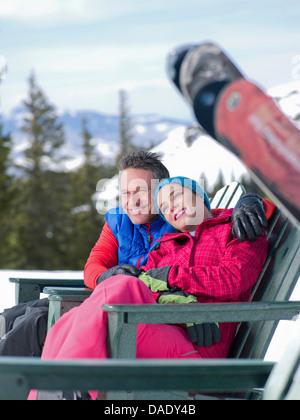 Reifer Mann und junge Frau, die gemeinsam entspannen, im Skigebiet - Stockfoto