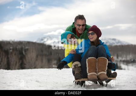 Drei Freunde sitzen auf Schlitten im Schnee - Stockfoto
