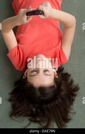 Brünette Mädchen auf Boden liegend, von oben - Stockfoto