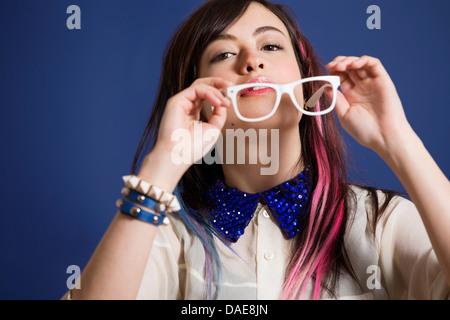 Porträt der jungen Frau mit gefärbten Haaren hält Gläser - Stockfoto