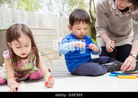 Mutter und zwei Kinder, die Zeichnung im Garten - Stockfoto