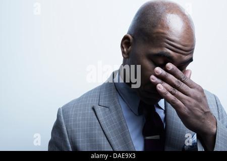 Studio-Porträt der Geschäftsmann mit der Hand über die Augen - Stockfoto