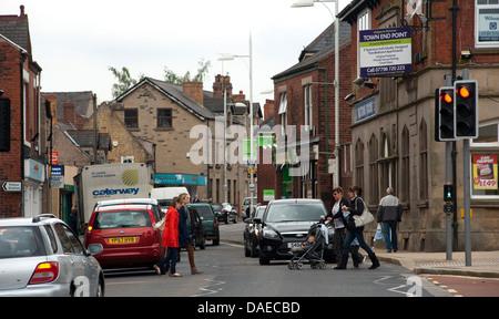 Fußgänger mit einer Kreuzung überqueren Sie eine Straße in der kleinen ländlichen Stadt Bolsover in Derbyshire, - Stockfoto