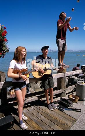 drei Jugendliche unterhalten Touristen in Sausalito auf Bridgeway Bürgersteig auf der Suche nach Tipps - Stockfoto