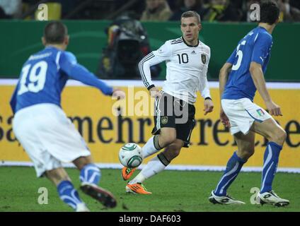 Deutschlands Lukas Podolski (C) steuert den Ball während das Freundschaftsspiel zwischen Deutschland und Italien - Stockfoto