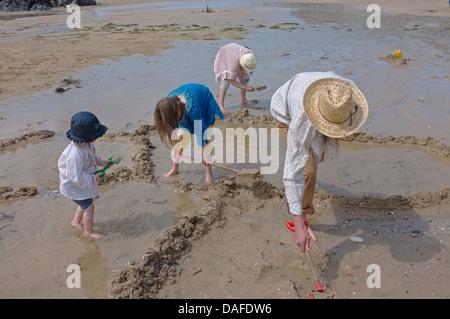 Ein Mann und seine Töchter bauen eine Sandburg am Strand in Cornwall, Großbritannien - Stockfoto