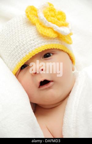 Baby mit einer weißen Mütze mit einer Blume - Stockfoto
