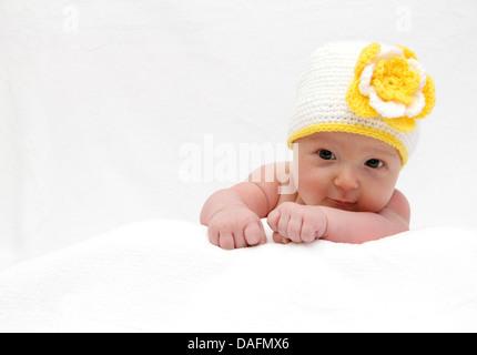 Baby mit einem weißen Mütze Baby auf Magen - Stockfoto