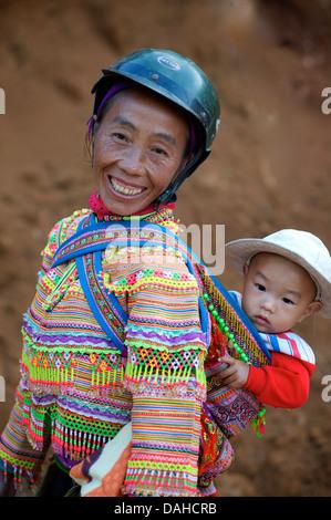 Flower Hmong Frau mit Kind in markanten tribal Kostüm. Können Sie Cau, in der Nähe von Bac Ha.  Vietnam. Modell veröffentlicht