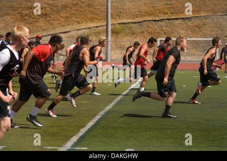 Multi-ethnischen Highschool-Athleten Protze mit Flexibilitätsübungen wie sie Frühjahr Fußballtraining in Kalifornien - Stockfoto