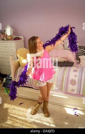 Eine acht Jahre altes Mädchen spielt mit einer Federboa in ihrem Schlafzimmer zu Hause in Laguna Beach, Kalifornien. - Stockfoto