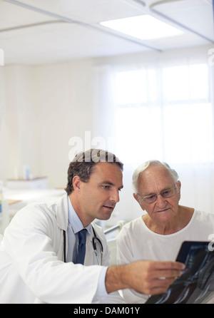 Arzt zeigt Röntgenbilder für ältere Patienten im Krankenzimmer - Stockfoto