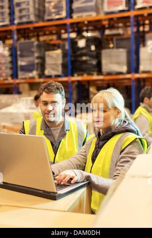 Arbeitnehmer mit Laptop im Lager - Stockfoto