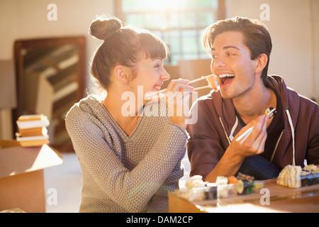 Paar Essen Sushi gemeinsam im neuen Zuhause - Stockfoto