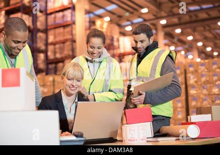 Geschäftsfrau und Arbeiter mit Laptop im Lager - Stockfoto