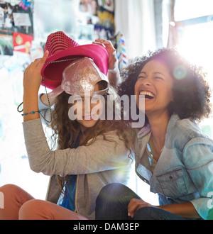 Frauen spielen mit Hüten im Schlafzimmer - Stockfoto