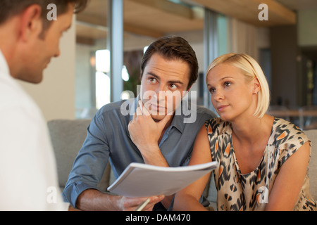 Finanzberater im Gespräch mit paar auf sofa - Stockfoto