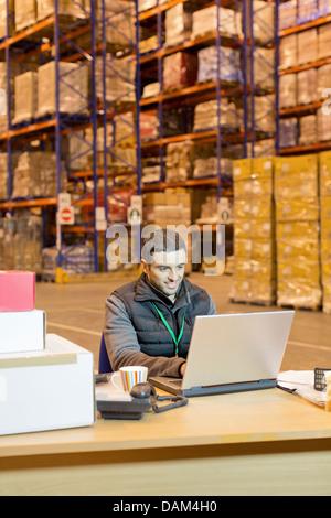Arbeiter mit Laptop im Lager - Stockfoto