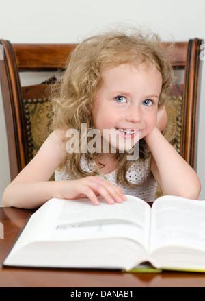 Niedliche kleine lächelnde Mädchen ein Buch zu lesen - Stockfoto