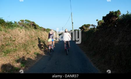 Zwei junge Frauen, Radfahren entlang einer Gasse auf einen frühen Sommerabend in St. Davids Pembrokeshire Wales - Stockfoto