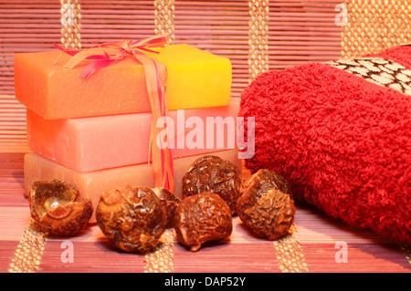 Handgemachte Seife, Waschnüsse und roten Handtuch auf das Bambus-Platzdeckchen. Wellness-Produkte - Stockfoto