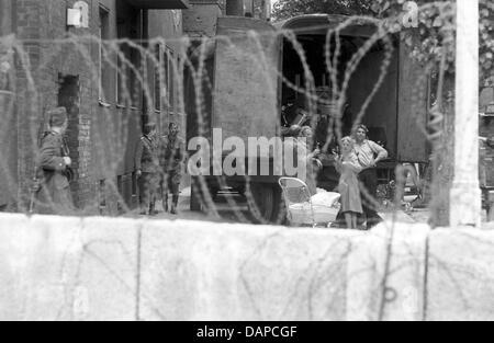 Datei - eine Archiv Bild datiert 1961 zeigt eine Familie hinter Stacheldraht, beobachtet von einem Polizeibeamten - Stockfoto
