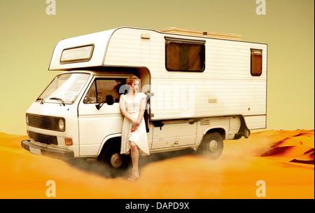 Deutschland, Berlin, junge Frau stand neben camping Bus in Wüste - Stockfoto