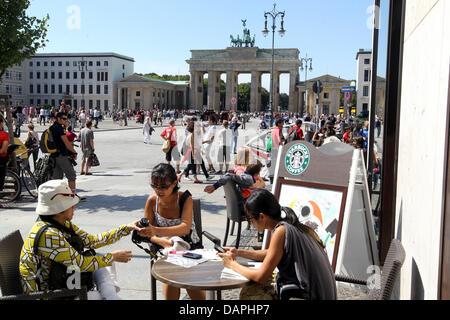 Mit Temperaturen um die 28 Grad bewohnen viele Touristen Pariser Elle vor dem Brandenburger Tor in Berlin, Deutschland, - Stockfoto