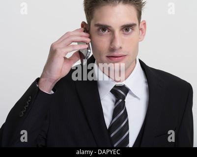 Geschäftsmann in Anzug und Krawatte mit Apple iPhone - Stockfoto