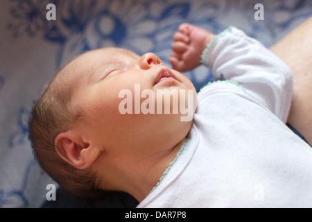 Neugeborenes Baby (2 Wochen alt) schläft auf der Eltern Knien - Stockfoto
