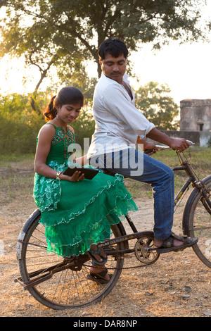 Indien, Agra, Uttar Pradesh junges Mädchen sitzen auf Fahrrad lesen Tablet-Gerät beobachtet von Vater in ländlicher - Stockfoto