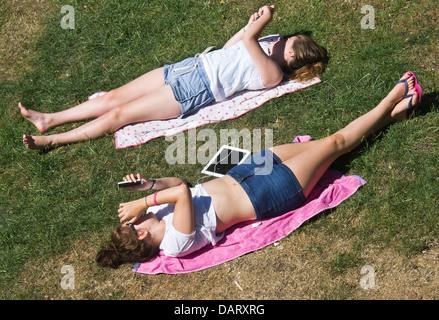 Mädchen im Teenageralter Sonnenbaden und mit ihren Smartphones. - Stockfoto