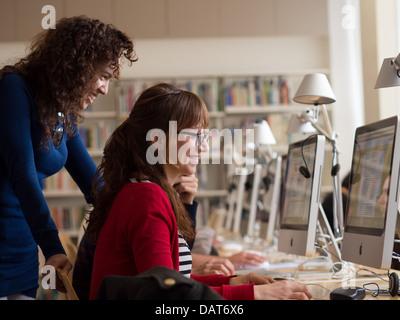 Zwei Frauen mit einem Apple iMac-Computer in der Bibliothek - Stockfoto