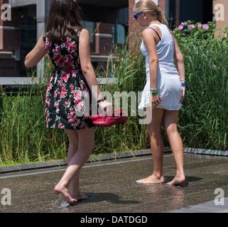 Besucher der High Line Park in New York erfrischen Sie ihre Füße in das Wasser-Funktion während der Hitzewelle - Stockfoto