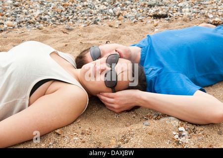 Ein junges Paar in ihren späten Teens oder in frühen zwanziger Jahren Sonnenbrille verlegen den Kopf an einem Strand - Stockfoto