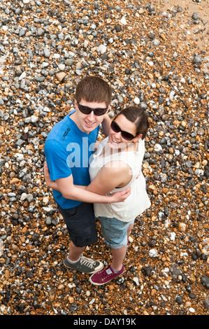 Draufsicht eines jungen Paares in ihren späten Teens oder in frühen zwanziger Jahren umarmt auf einem Kiesstrand - Stockfoto