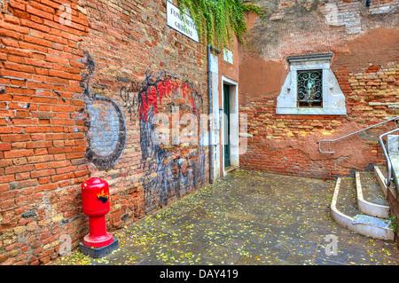 Kleinen Innenhof unter den alten Backsteinmauern mit Graffiti in Venedig, Italien. - Stockfoto