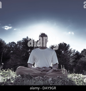 Chinesischer Mann meditieren im Freien bei Sonnenaufgang in der Natur, sitzen mit gekreuzten Beinen auf dem Rasen - Stockfoto