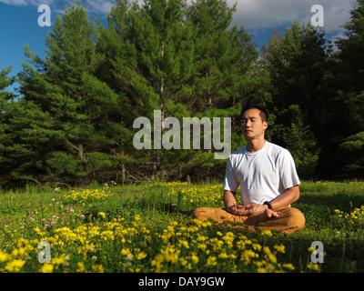 Asiatischer Mann bei Sonnenaufgang in der Natur, sitzt mit gekreuzten Beinen in grüne outdoor-Sommer-Natur-Landschaft - Stockfoto