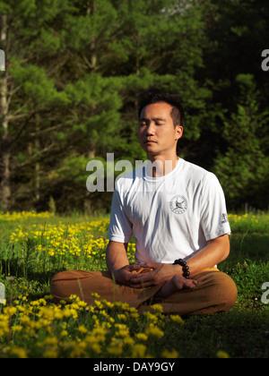 Toronto-Shaolin Schule Lehrer Dao meditieren im Freien bei Sonnenaufgang in der Natur, sitzen mit gekreuzten Beinen - Stockfoto