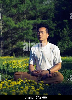 Künstlerische Outdoor-Foto von einem asiatischen Mann praktizieren chinesische buddhistische Meditation bei Sonnenaufgang - Stockfoto