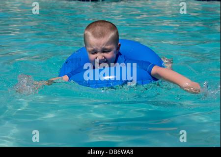 Ein sechs Jahre alter Junge mit Autismus reagiert auf Plantschen im Pool. - Stockfoto
