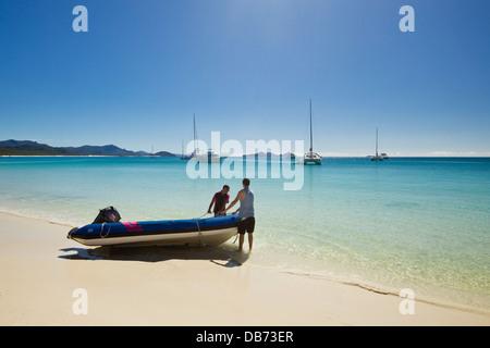 Männer tragen eine Jolle in das klare Wasser des Whitehaven Beach. Whitsunday Island, Whitsundays, Queensland, Australien - Stockfoto