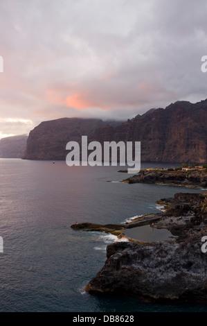 Los Gigantes Klippen, Dorf und Küste in der Dämmerung an einem bewölkten Sommertag mit tiefen, satten Farben, die - Stockfoto