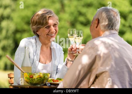 Glücklich Senioren klirrende Gläser im Garten - Stockfoto